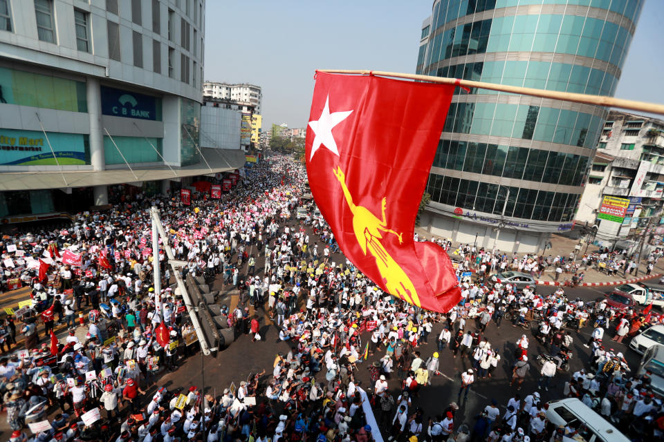 Anti-coup protesters gather outside the Hledan Centre while the flag of the National League for Democracy party is waved from an overhead roadway in Yangon, Myanmar Monday, Feb. 22, 2021. Protesters gathered in Myanmar's biggest city Monday despite the ruling junta's thinly veiled threat to use lethal force if people answered a call for a general strike opposing the military takeover three weeks ago.(AP Photo)