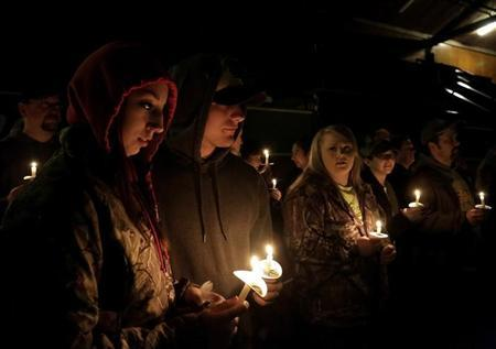 Members of communities affected by the Oso mudslide participate a candlelight vigil at the Community Center in Darrington, Washington