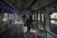 Pro-democracy protesters vandalize a train parked inside the Chinese University MTR station in Hong Kong, Wednesday, Nov. 13, 2019. Protesters in Hong Kong battled police on multiple fronts on Tuesday, from major disruptions during the morning rush hour to a late-night standoff at a prominent university, as the 5-month-old anti-government movement takes an increasingly violent turn. (AP Photo/Kin Cheung)