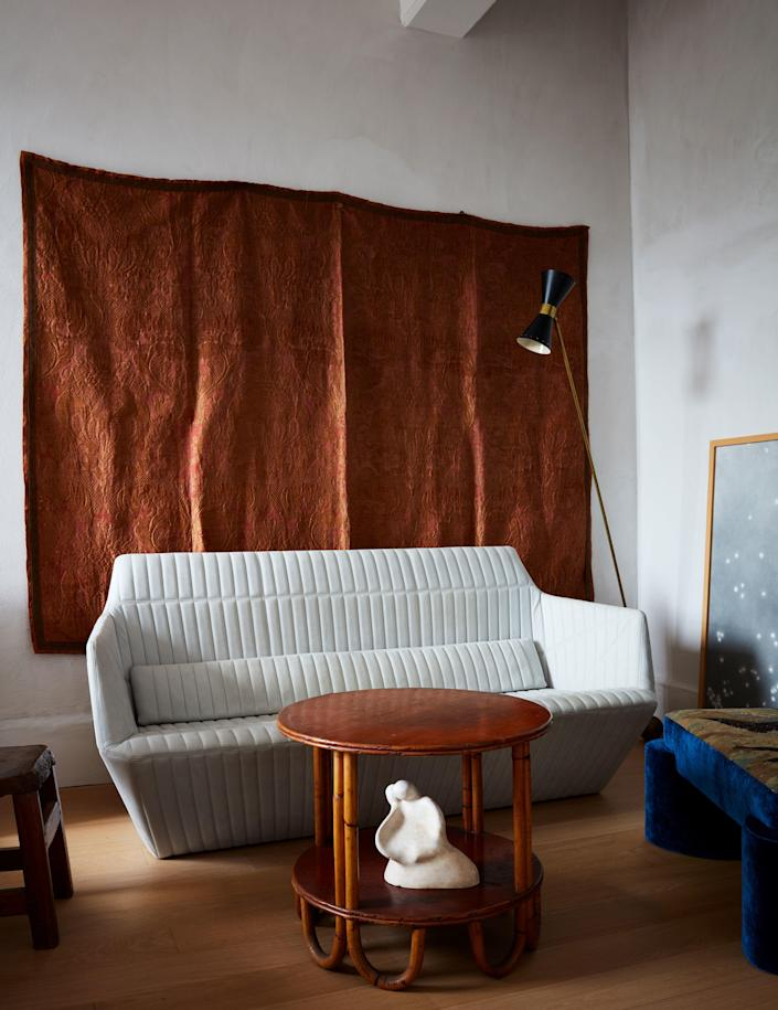 In the bedroom sitting area, an 18th century Italian silk tapestry hangs behind a Facett sofa by Ronan and Erwan Bouroullec for Ligne Roset, a vintage bamboo side table, a tapestry-covered chair by Valle, a vintage Stilnovo lamp, and a painting by Katherine Keltner.