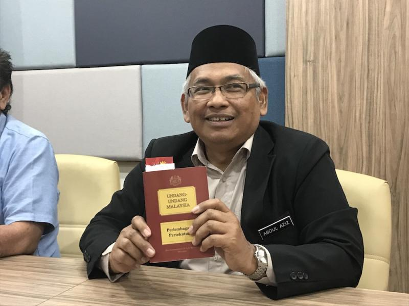 Perak DAP vice-chairman Abdul Aziz Bari holds a copy of the Federal Constitution at the State Secretariat Building in Ipoh December 11, 2019. — Picture by John Bunyan