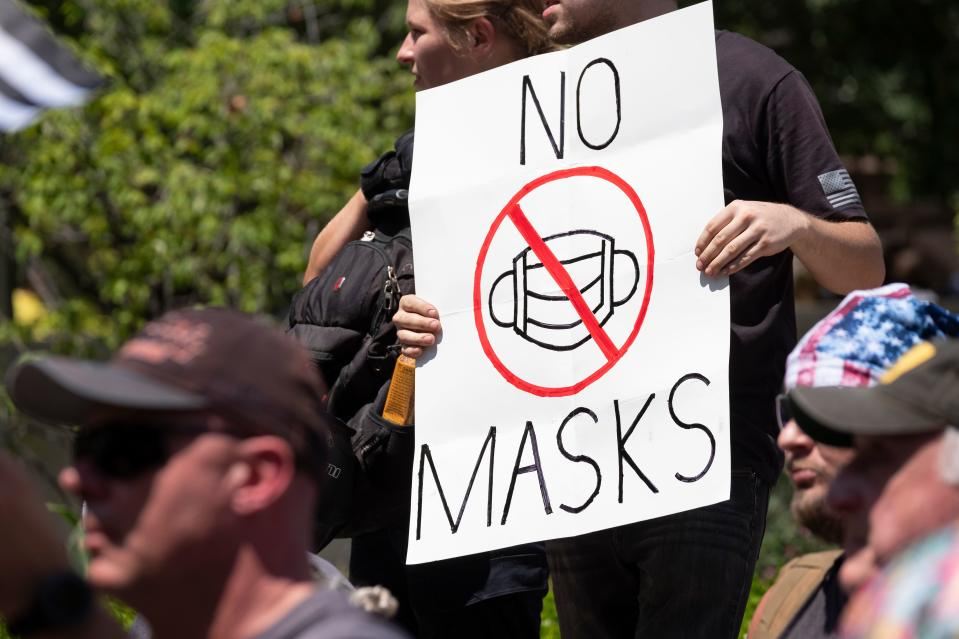 "An anti-mask protestor holds up a sign in front of the Ohio Statehouse during a right-wing protest ""Stand For America Against Terrorists and Tyrants"" at State Capitol on July 18, 2020 in Columbus, Ohio. - Protestors descended on Columbus, Ohio for a planned anti-mask rally in response to local laws requiring people to wear a mask in many Ohio cities. (Photo by Jeff Dean / AFP) (Photo by JEFF DEAN/AFP via Getty Images)"