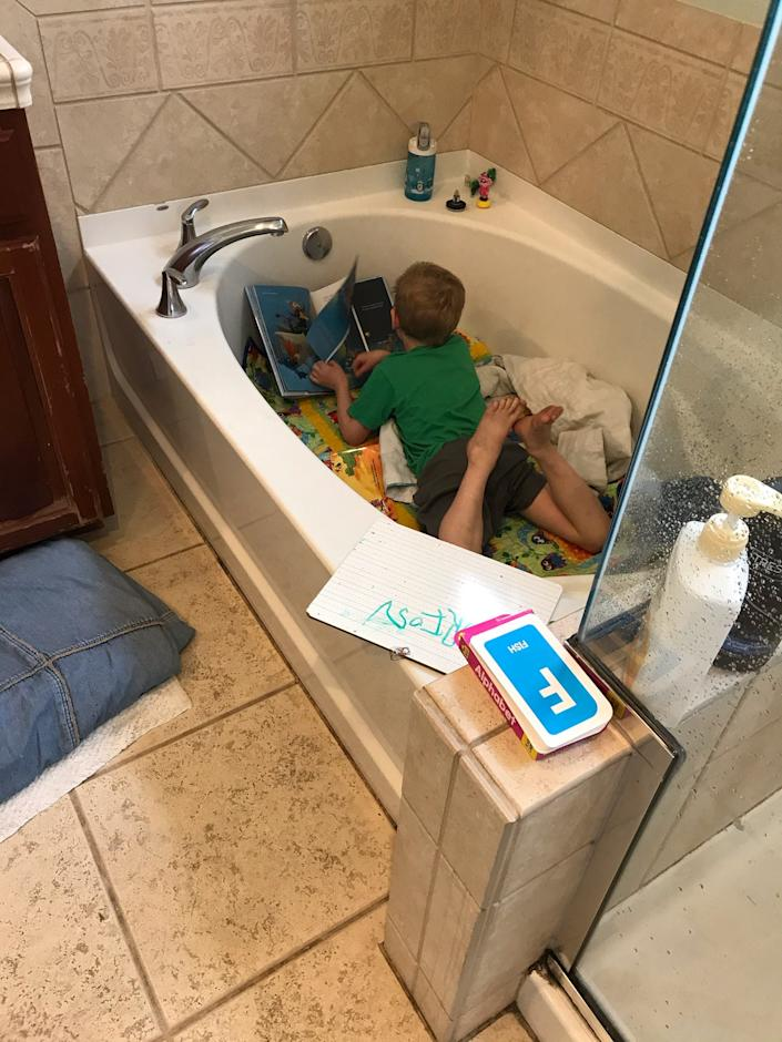 """Orion Carlson, age 4, learning phonics from his makeshift classroom """"tub"""" at home in Alameda, California."""