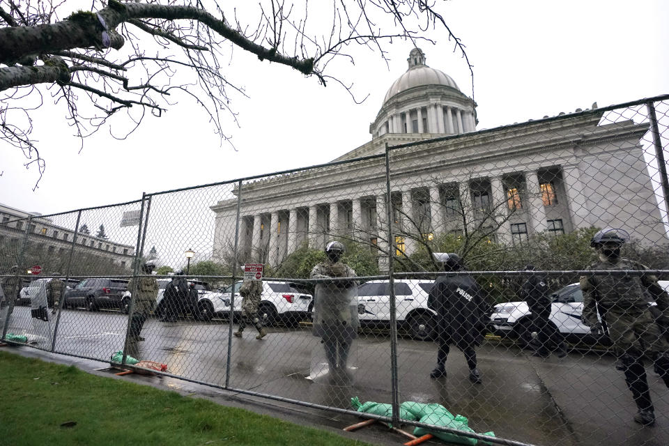 Members of the Washington National Guard stand near a fence surrounding the Capitol in anticipation of protests Monday, Jan. 11, 2021, in Olympia, Wash. State capitols across the country are under heightened security after the siege of the U.S. Capitol last week. (AP Photo/Ted S. Warren)