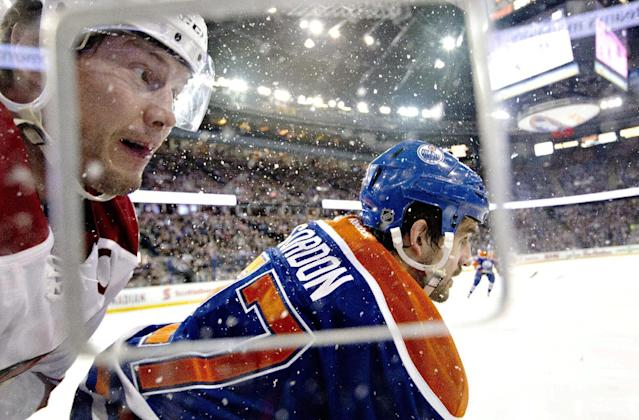 Phoenix Coyotes' Shane Doan (19) is checked by Edmonton Oilers' Boyd Gordon (27) during the first period of an NHL hockey game Friday, Jan. 24, 2014, in Edmonton, Alberta. (AP Photo/The Canadian Press, Jason Franson)