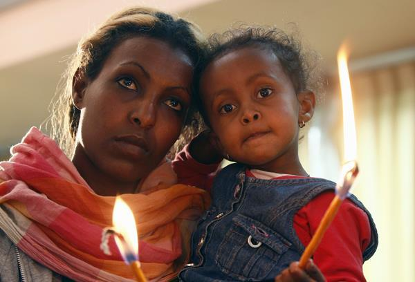 An Eritrean refugee with her daughter in hand hold candles during a memorial gathering to mark the first anniversary of the Lampedusa migrant shipwreck.