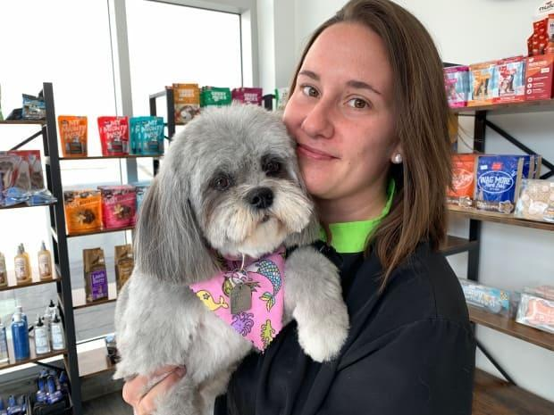 Natalie Ulaszonek, a manager and groomer at Marda Loop Doggie Daycare & Spa, with one of her clients. (David Bell/CBC - image credit)