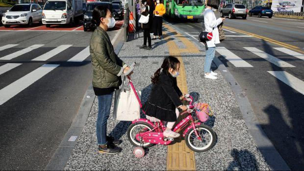 A mother and her child wearing protective face masks as they cross the street