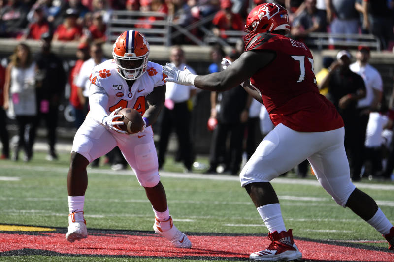Clemson defensive tackle Nyles Pinckney (44) makes an interception away from the defense of Louisville offensive lineman Mekhi Becton (73) during the first half of an NCAA college football game in Louisville, Ky., Saturday, Oct. 19, 2019. (AP Photo/Timothy D. Easley)