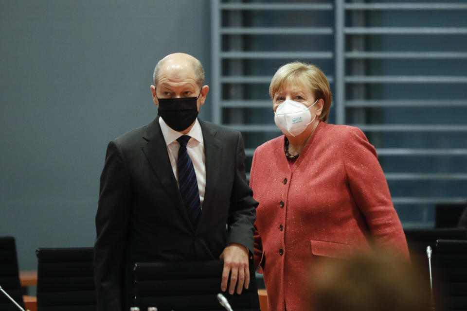 FILE - In this Nov. 11, 2020 file photo, German Chancellor Angela Merkel, right, and German Finance Minister Olaf Scholz arrive at the weekly cabinet meeting of the German government at the chancellery in Berlin, Germany. German lawmakers presenting a report into the collapse of payment processing company Wirecard accused the country's finance minister and auditors Ernst and Young of numerous oversight failings. (AP Photo/Markus Schreiber, Pool, File)