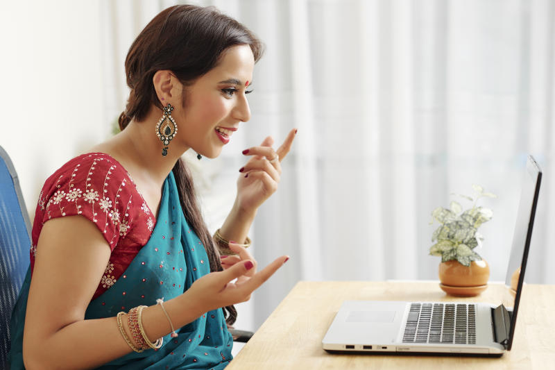 Cheerful beautiful Indian woman sitting in front on opened laptop and video calling her hands