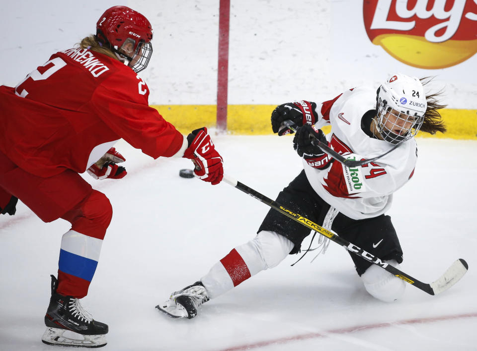 Switzerland's Noemi Ryhner, right, tries to get the puck past Russia's Angelina Goncharenko during the second period of an IIHF women's hockey championships game in Calgary, Alberta, Saturday, Aug. 21, 2021. (Jeff McIntosh/The Canadian Press via AP)