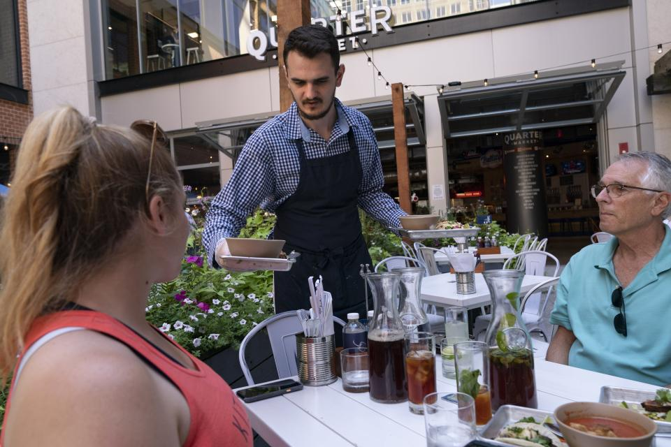 """After they ordered on an app via a barcode attached to the table, Bjanko Zeqiri, a food runner at Bartaco, brings their lunches to restaurant patrons as they sit on the patio at Bartaco, in Arlington, Va., on Thursday, Sept. 2, 2021. The restaurant is using an automated app for ordering and payments. Instead of servers Bartaco uses """"food runners"""" to bring the orders to the tables. (AP Photo/Jacquelyn Martin)"""