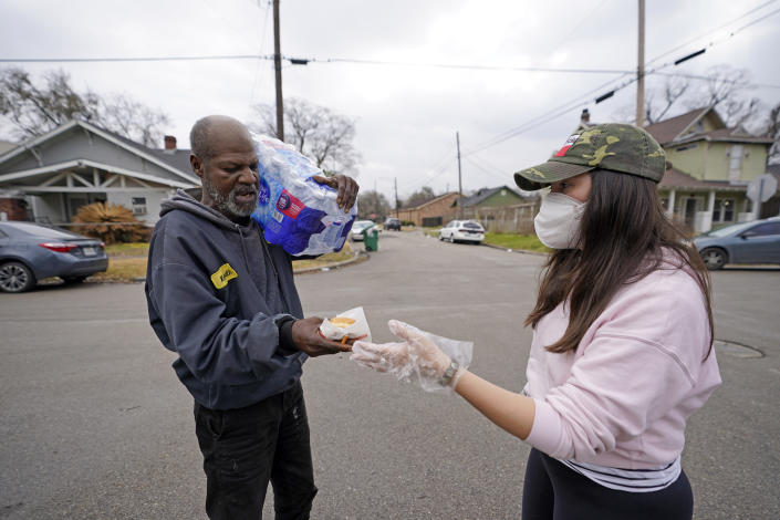 Jacqueline Westman, right, hands a donut to Kenneth Henderson while also helping distribute donated water to residents without running water in their homes, Friday, Feb. 26, 2021, in Houston. Local officials, including Houston Mayor Sylvester Turner, say they have focused their efforts during the different disasters on helping the underserved and under-resourced but that their work is far from complete. (AP Photo/David J. Phillip)