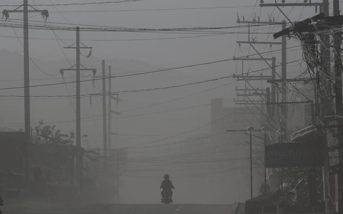 A motorcycle rider drives along a street as wind blows volcanic ash from Taal volcano at a deserted town in Lemery, Batangas province, southern Philippines on Thursday Jan. 16, 2020. Taal volcano belched smaller in plumes of ash Thursday but shuddered continuously with earthquakes and cracked roads in nearby towns, which were blockaded by police due to fears of a bigger eruption. (AP Photo/Aaron Favila)