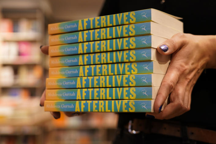 """A member of staff holds a pile of copies of """"Afterlives"""" by Zanzibar-born novelist Abdulrazak Gurnah in a book shop in London, Thursday, Oct. 7, 2021. U.K.-based Tanzanian writer Abdulrazak Gurnah, whose experience of crossing continents and cultures has fed his novels about the impact of migration on individuals and societies, won the Nobel Prize for Literature on Thursday. (AP Photo/Alberto Pezzali)"""