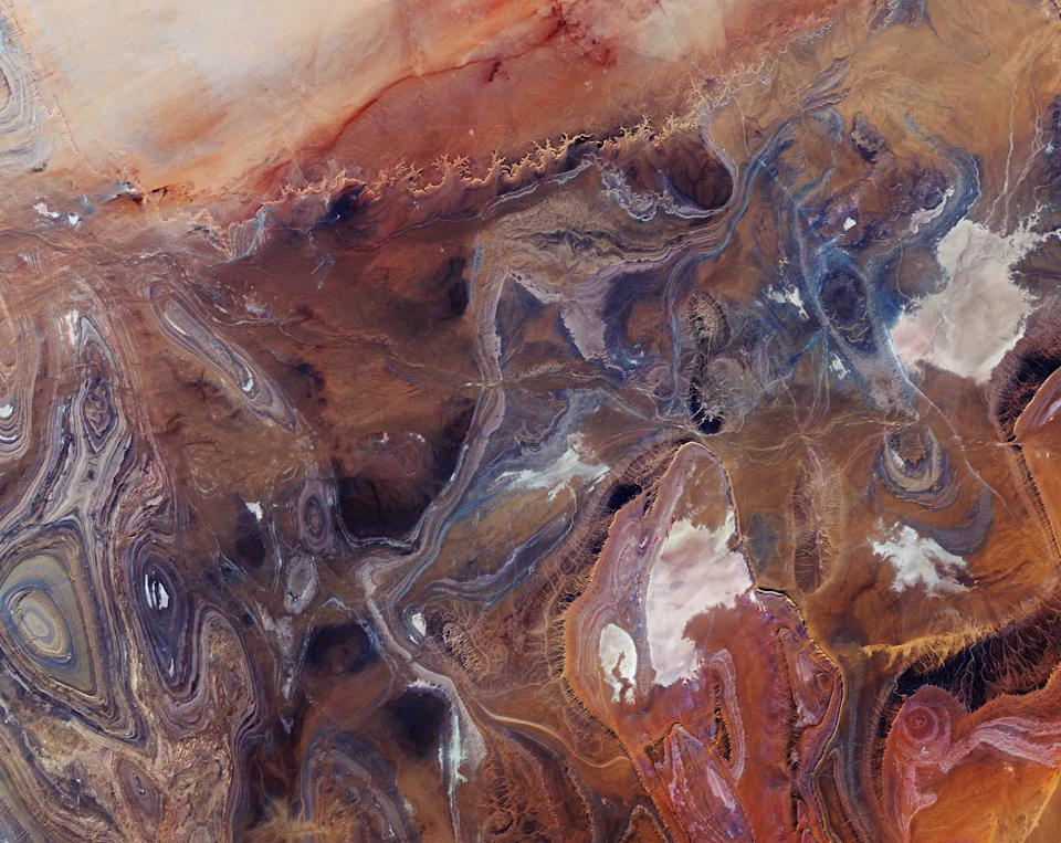 "This stunning, sandy, sienna-hued landscape is the Tanezrouft Basin (a desolate region of the Sahara Desert) as seen by the Copernicus Sentinel-2 from space. The extremely arid plain is home to scorching temperatures, little water and vegetation and has even been nicknamed the ""Land of Terror."" This image was captured as part of Copernicus Sentinel-2, a two-satellite mission that is part of the European Space Agency's Copernicus program."