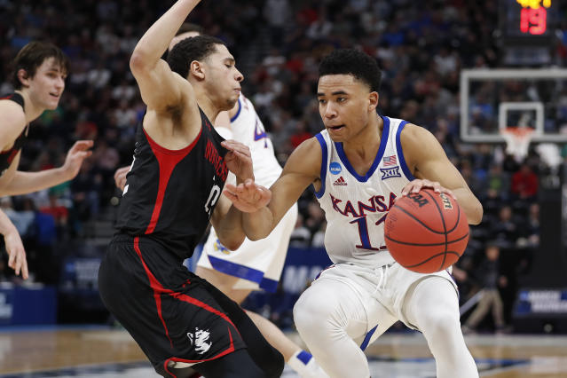 Northeastern guard Jordan Roland defends against Kansas guard Devon Dotson (11) in the first half during a first round men's college basketball game in the NCAA Tournament Thursday, March 21, 2019, in Salt Lake City. (AP Photo/Jeff Swinger)