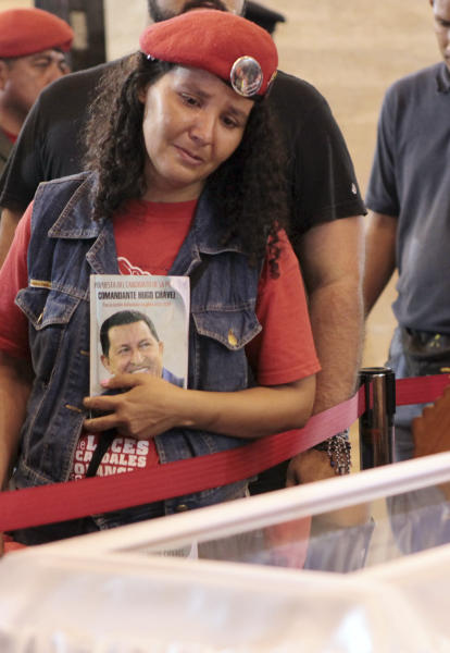 In this photo released by Miraflores Press Office, a mourner weeps as she looks into the glass-topped casket containing the remains of Venezuela's late President Hugo Chavez as his body lies in state at the military academy in Caracas, Thursday, March 7, 2013. Chavez died of a massive heart attack Tuesday after great suffering and inaudibly mouthed his desire to live, the head of Venezuela's presidential guard said late Wednesday. (AP Photo/Miraflores Presidential Press Office)