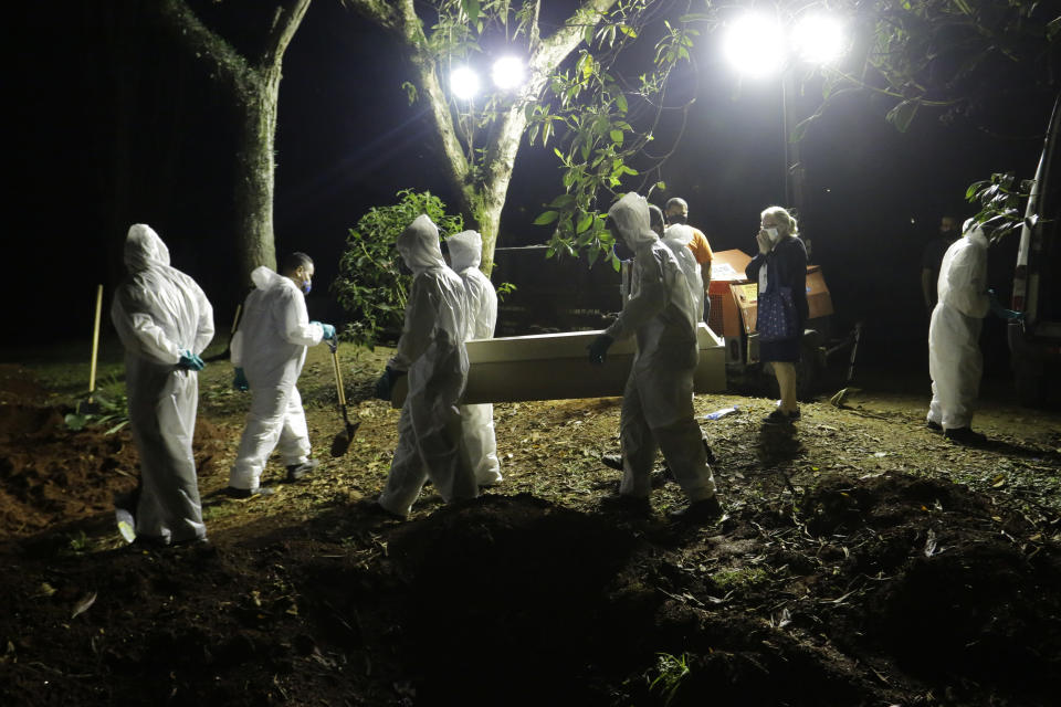 Cemetery workers in white overalls carry the coffin of a COVID-19 victim to his grave at the Vila Formosa cemetery in Sao Paulo, Brazil, under spotlights.