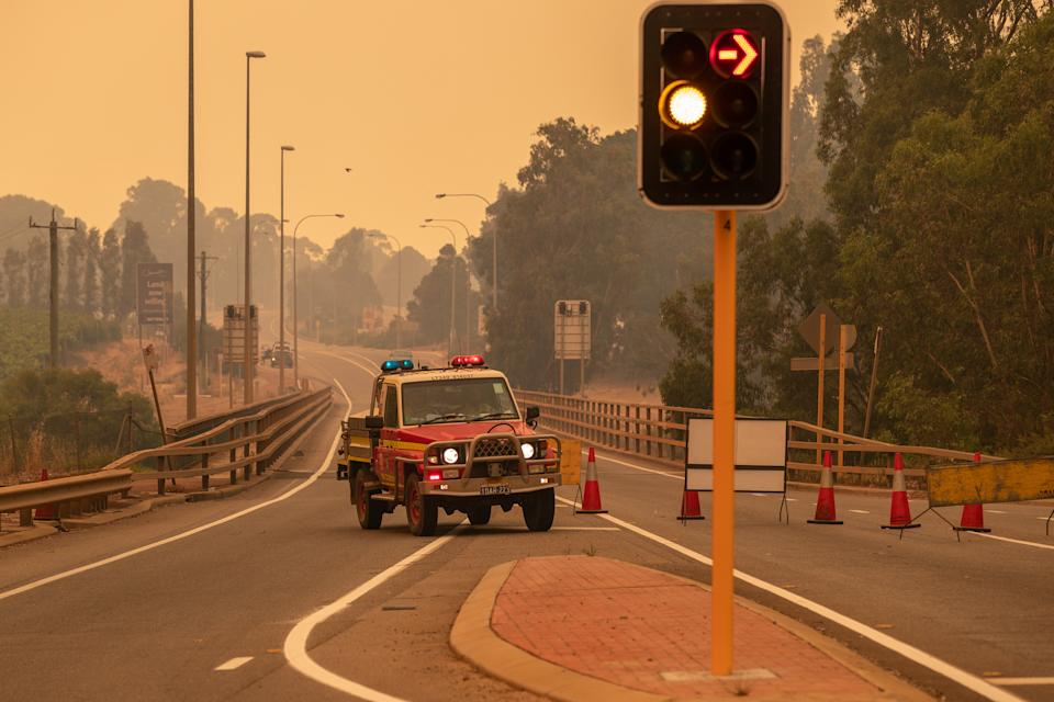 Emergency vehicles block a road heading towards the fire. Source: AAP