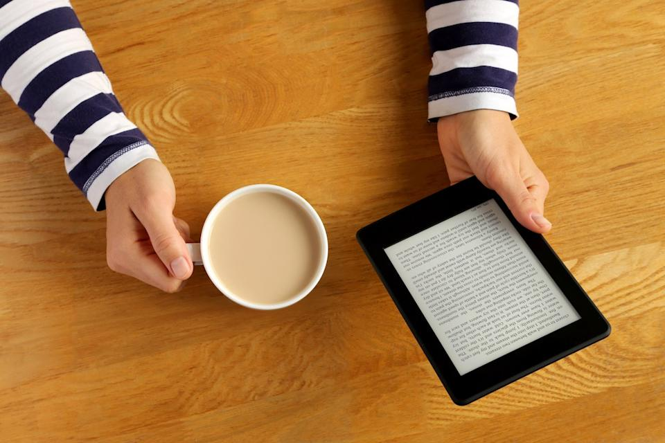Woman reading a novel on a tablet and drinking her coffee.
