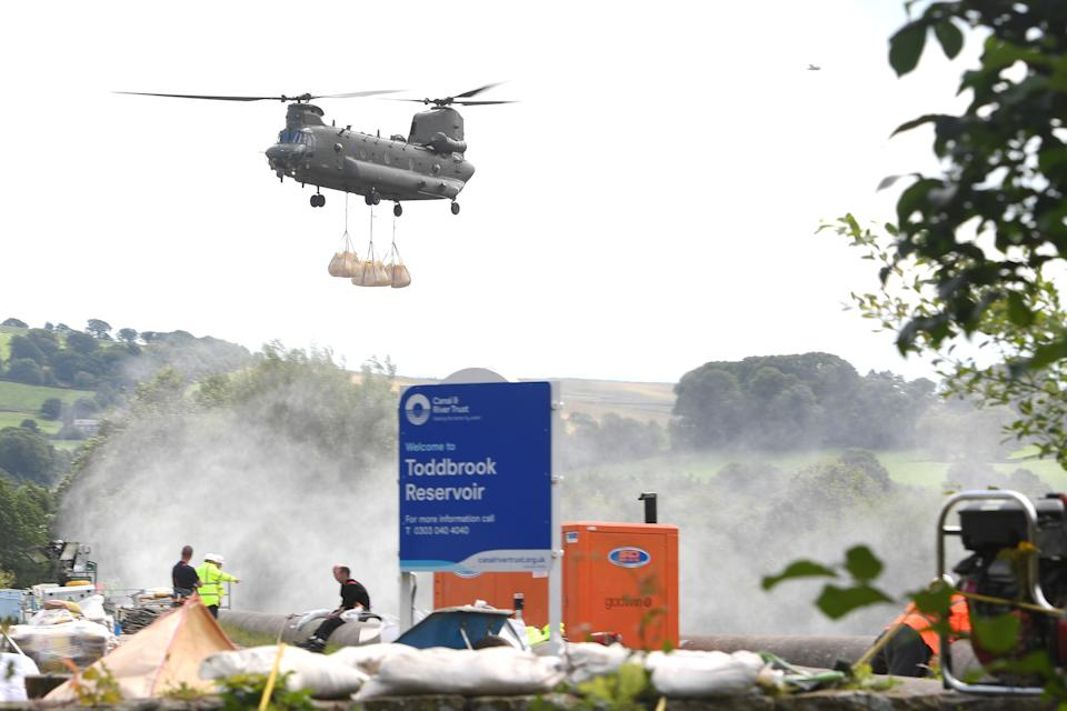 A Royal Air Force Chinook transports sandbags as work continues to shore up the dam at Toddbrook Reservoir near the village of Whaley Bridge, Derbyshire, after it was damaged in heavy rainfall.