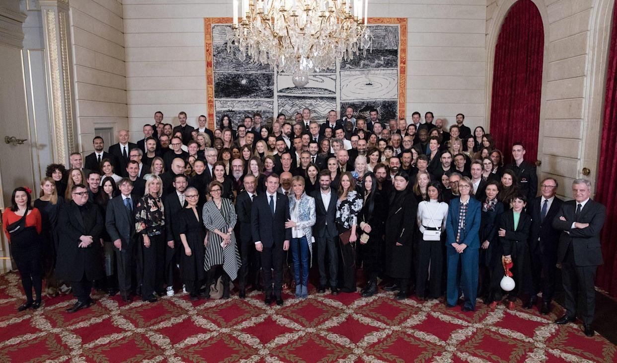 President Emmanuel Macron and his wife, Brigitte, center, host a group of fashion designers and industry executives at the Elysée Palace for a Paris Fashion Week dinner in early March. Abloh is in the second to last row on the right side of the photo. (Photo: Soazig de la Moissonnière/Présidence de la République)