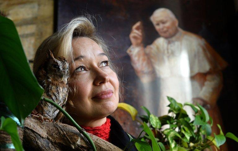 Natalia Tsarkova poses with her pet owl next to a painting of Pope John Paul II at her Rome studio on December 18, 2012
