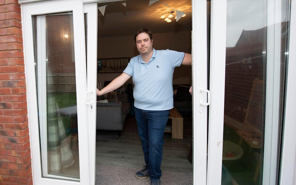 Ryan Kirkaldy demonstrates the faulty patio doors on his home - Dale Cherry