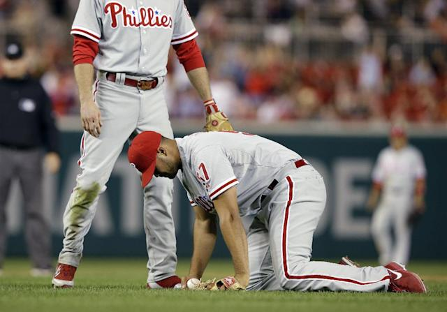 Philadelphia Phillies relief pitcher Luis Garcia, right, holds the ball after being hit by a two RBI single by Washington Nationals' Wilson Ramos, with second baseman Chase Utley, left, during the fifth inning of a baseball game at Nationals Park, Friday, Sept. 13, 2013, in Washington. (AP Photo/Alex Brandon)