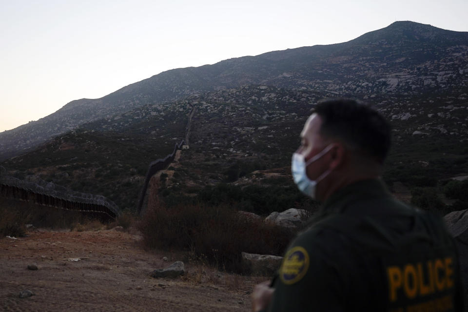 Border Patrol agent Justin Castrejon looks toward where the border wall makes its way over a mountain Thursday, Sept. 24, 2020, near Tecate, Calif. President Donald Trump's reshaping of U.S. immigration policy may be most felt in his undoing of asylum. Castrejon says migrants pay $8,000 to $10,000 to be guided through the mountains and picked up by a driver once they reach a road. (AP Photo/Gregory Bull)