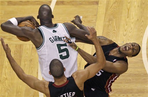 Miami Heat guard Mario Chalmers, right, reacts as he starts to fall to the floor after Boston Celtics forward Kevin Garnett landed an elbow on him during a struggle for the ball during the fourth quarter of Game 3 in the NBA basketball playoffs Eastern Conference finals, in Boston on Friday, June 1, 2012. At bottom is Heat forward Shane Battier. (AP Photo/Charles Krupa)