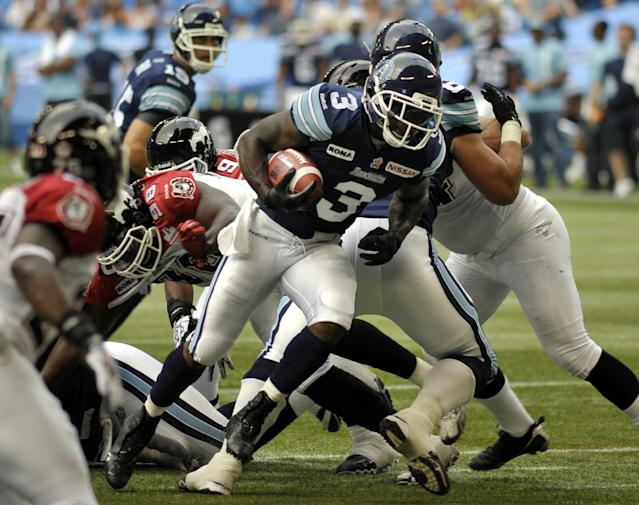 Toronto Argonauts running back Cory Boyd, left, carries the ball during 1st half CFL action against the Calgary Stampeders in Toronto, Saturday, July 7, 2012. (CFL PHOTO - J.P. Moczulski)
