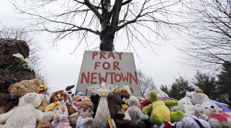FILE - In this Dec. 17, 2012 file photo, stuffed animals and a sign calling for prayer sit at the base of a tree near the Newtown VIllage Cemetery in Newtown, Conn., after 26 people were shot to death at Sandy Hook Elementary School. Newtown officials and families of those killed have given away 63,790 stuffed animals and thousands of other gifts that poured into the town in the weeks following the massacre. The final boxes of toys and school supplies were shipped out of the warehouse on March 29, 2013. (AP Photo/Charles Krupa, File)