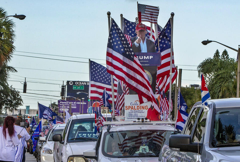 In this Oct. 10, 2020 photo, a caravan supporting President Trump drives around Miami streets. Florida's Cuban American voters remain a bright spot in Trump's effort to retain his winning coalition from 2016. Polls show his strong support from these key voters may even be growing to include the younger Cuban Americans that Democrats once considered their best hope of breaking the GOP's hold. (Pedro Portal/Miami Herald via AP)