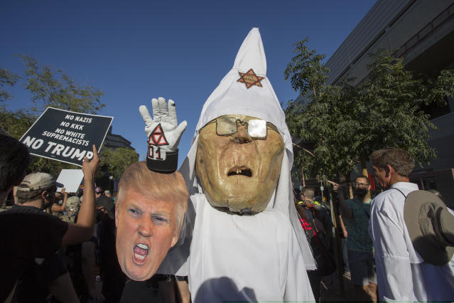 A protester wears a costume likeness of Sheriff Joe Arpaio as a member of the KKK with a caricature of President Trump outside the Phoenix Convention Center, Aug. 22, 2017, in Phoenix. (Photo: David McNew/Getty Images)