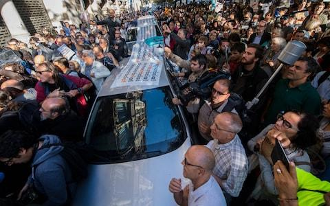 People surround Spanish Civil Guard Police cars outside the Catalan Vice-President and Economy office as police officers hold a searching operation inside on September 20 - Credit: David Ramos/Getty Images
