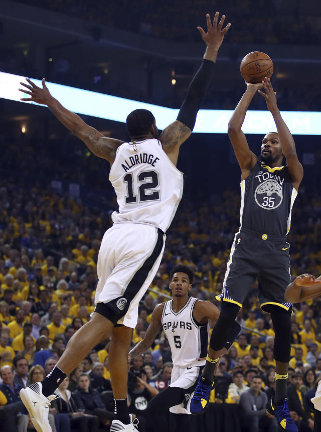 Golden State Warriors' Kevin Durant, right, shoots against San Antonio Spurs' LaMarcus Aldridge (12) during the first quarter in Game 2 of a first-round NBA basketball playoff series Monday, April 16, 2018, in Oakland, Calif. (AP Photo/Ben Margot)
