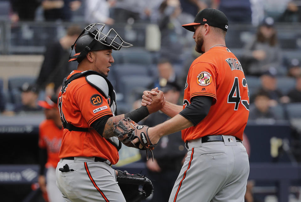Baltimore Orioles catcher Jesus Sucre, left, congratulates relief pitcher Mike Wright (43) after the Orioles defeated the New York Yankees 5-3 in a baseball game, Saturday, March 30, 2019, in New York. (AP Photo/Julie Jacobson)