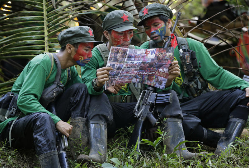 FILE - In this Nov. 23, 2016, file photo, members of the New People's Army communist rebels with face painted to conceal their identities, reads a local paper at their guerrilla encampment tucked in the harsh wilderness of the Sierra Madre mountains southeast of Manila, Philippines. Justice officials have asked a court to formally designate the Communist Party of the Philippines and its armed wing, the New People's Army, as terrorist groups in a move that could further damage chances of a resumption of stalled peace talks. (AP Photo/Aaron Favila, File)