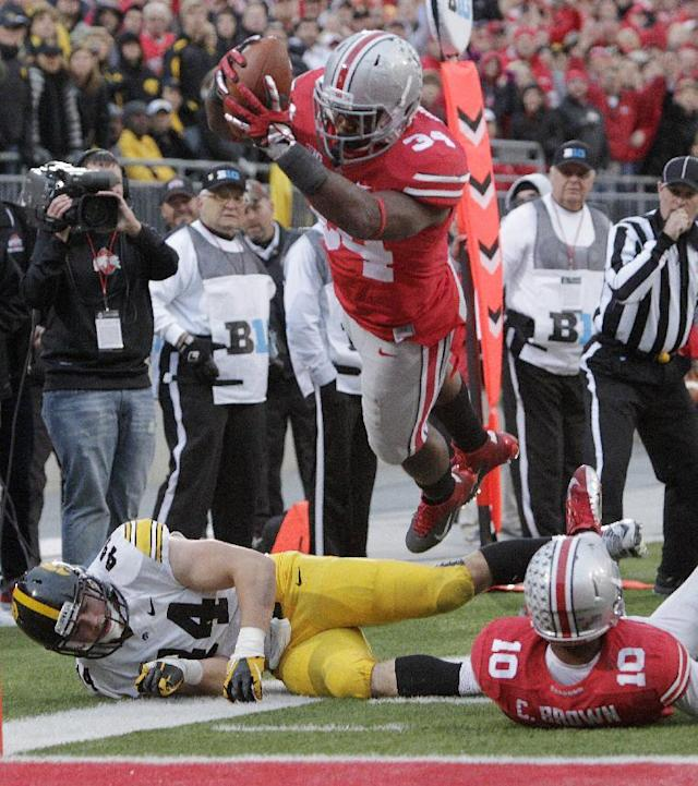 Ohio State running back Carlos Hyde, top, dives over the goal line to score a touchdown past teammate Corey Brown, right, and Iowa linebacker James Morris during the fourth quarter of an NCAA college football game Saturday, Oct. 19, 2013, in Columbus, Ohio. Ohio State beat Iowa 34-24. (AP Photo/Jay LaPrete)