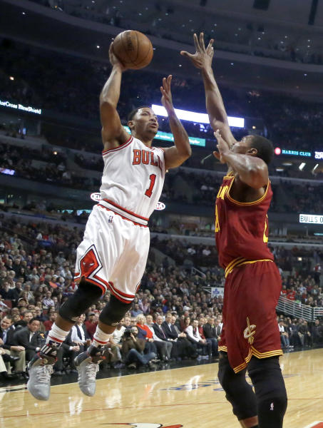 Chicago Bulls point guard Derrick Rose (1) shoots the ball over Cleveland Cavaliers center Andrew Bynum during the first half of an NBA basketball game Monday, Nov. 11, 2013, in Chicago. (AP Photo/Charles Rex Arbogast)