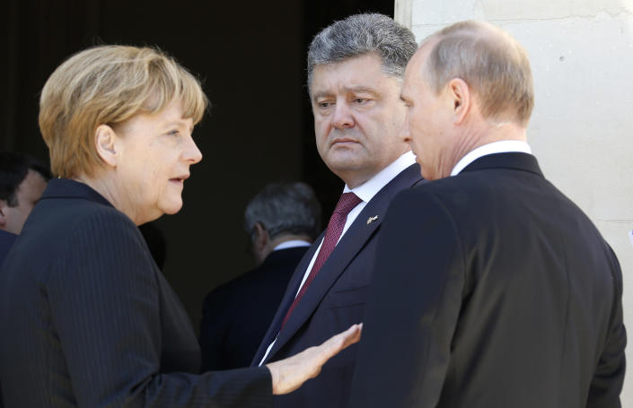 FILE - In this June 6, 2014, file photo, German Chancellor Angela Merkel, left, Russian President Vladimir Putin, right, and then Ukrainian president-elect Petro Poroshenko, center, talk as they take part in the 70th anniversary of D-Day in Benouville in Normandy, France. After a series of Ukraine's military defeats, France and Germany helped broker a peace deal that was signed in February 2015 in the Belarusian capital of Minsk. (Regis Duvignau/Pool Photo via AP, File)