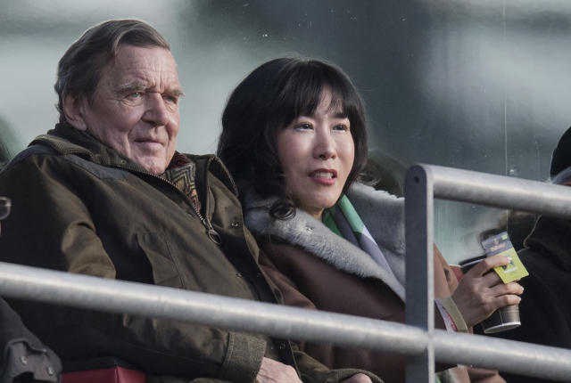Former German Chancellor Gerhard Schroeder, left, and his South Korean fiancee Kim So-yeon watch the German Bundesliga soccer match between Hannover 96 and Borussia Moenchengladbach in Hannover, northern Germany, Saturday, Feb. 24, 2018. (Julian Stratenschulte/dpa via AP)