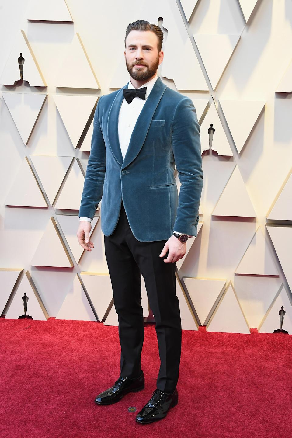 """<p>The """"Captain America"""" start put a high fashion spin on the traditional red carpet tux by opting for a slate blue velvet jacket. (Image via Getty Images) </p>"""