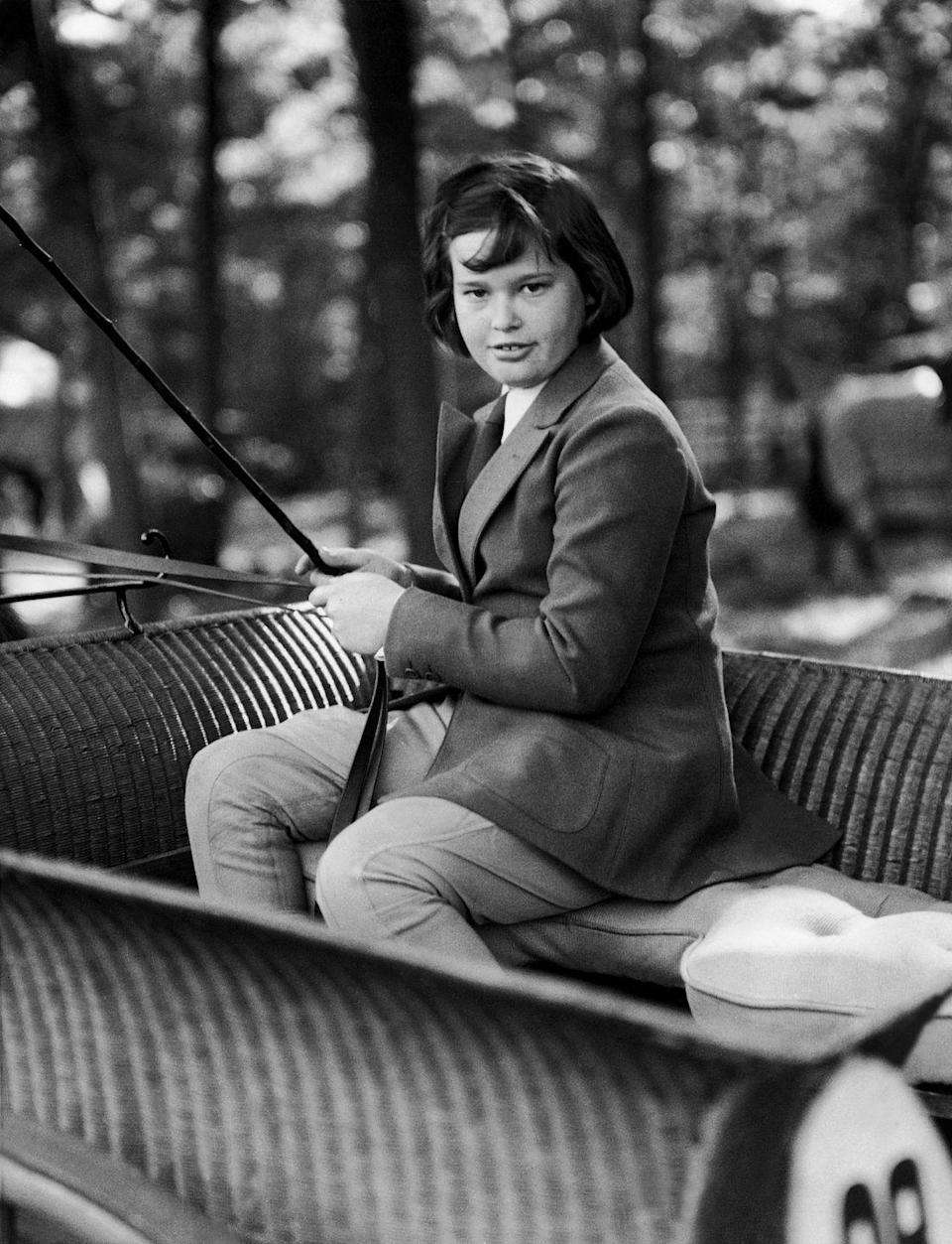 <p>A young Gloria sits in a horse-drawn carriage in Locust Valley, New York in 1935.</p>