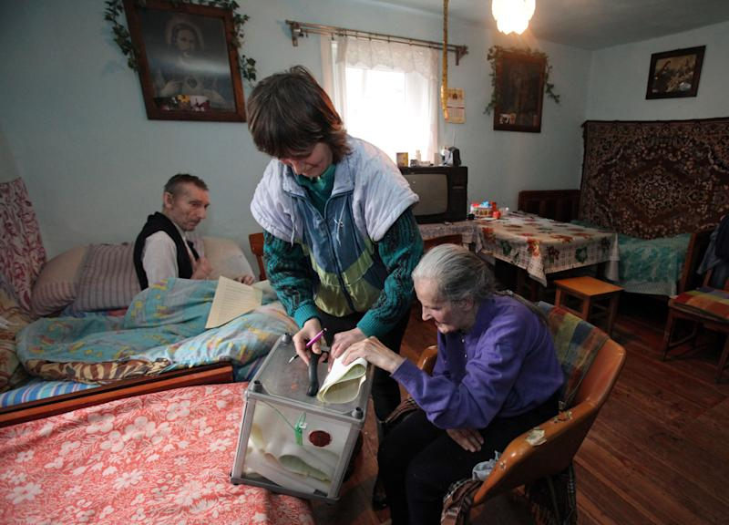 Ukrainian Stefaniya Rogulya, 79, foreground casts her ballots, at her home, with her husband Roman, in the background, in Polany village, Western Ukraine, Sunday, Oct. 28, 2012. Ukrainians are electing a parliament on Sunday in a crucial vote tainted by the jailing of top opposition leader Yulia Tymoshenko and fears of election fraud. (AP Photo/Petro Zadorozhnyy)