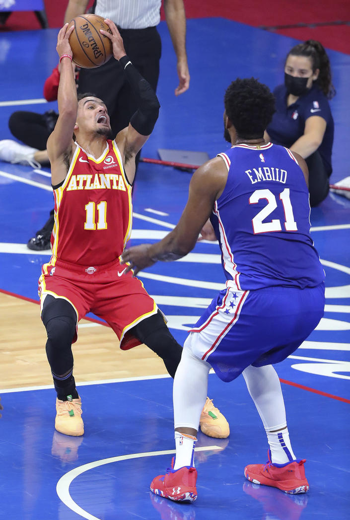 Atlanta Hawks guard Trae Young is defended by Philadelphia 76ers center Joel Embiid during Game 2 of an NBA basketball Eastern Conference semifinal series Tuesday, June 8, 2021, in Philadelphia. (Curtis Compton/Atlanta Journal-Constitution via AP)