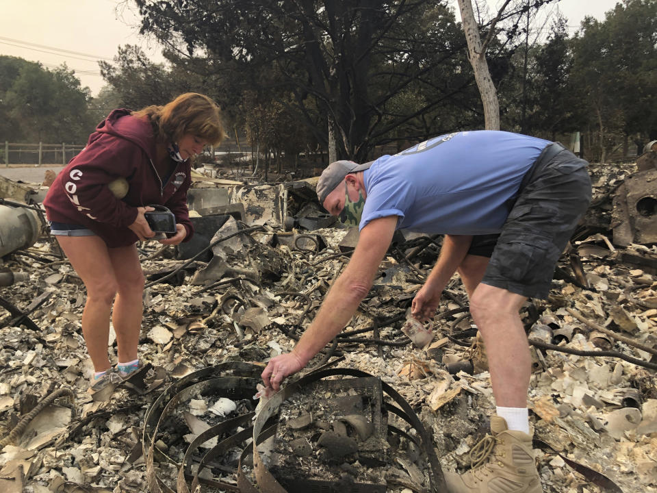 """Kevin Conant and his wife, Nikki, sift through debris of their burnt home and business """"Conants Wine Barrel Creations,"""" after the Glass/Shady fire completely engulfed it, Wednesday, Sept. 30, 2020, in Santa Rosa, Calif. The Conants escaped with their lives, which we are grateful for, but they barely made it out with the clothes on their backs in the wake of the fire. The Glass and Zogg fires are among nearly 30 wildfires burning in California. (AP Photo/Haven Daley)"""
